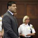 Former New England Patriots NFL football player Aaron Hernandez stands as the judge enters the courtroom before Hernandez's arraignment at Suffolk Superior Court, Thursday, May 21, 2015, in Boston, on a charge of trying to silence a witness in a double murder case against him by shooting the man in the face. (AP Photo/Stephan Savoia, Pool)
