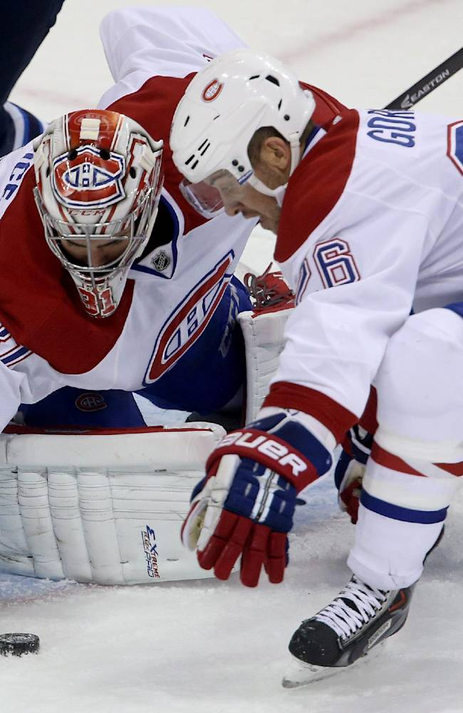 Montreal Canadiens' goaltender Carey Price (31) and Josh Gorges (26) try to cover a loose puck that stopped just outside the crease during the first period of an NHL hockey game against the Winnipeg Jets in Winnipeg, Manitoba, Tuesday, Oct. 15, 2013
