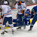 Vancouver Canucks' Ryan Stanton (18) is tripped up by Edmonton Oilers' Teddy Purcell (16) while battling for control of the puck with Oilers' Jordan Eberle (14) during the second period of an NHL hockey preseason game Saturday, Oct. 4, 2014, in Vancouver,