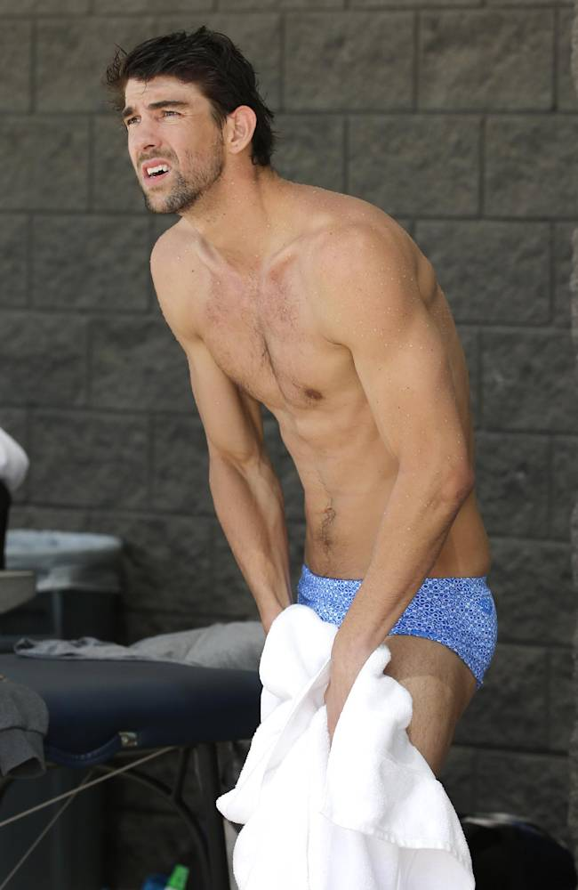 Michael Phelps dries off after warm ups prior to competing in the 100-meter butterfly during the Arena Grand Prix swim meet, Thursday, April 24, 2014, in Mesa, Ariz. It is Phelps' first competitive event after a nearly two-year retirement