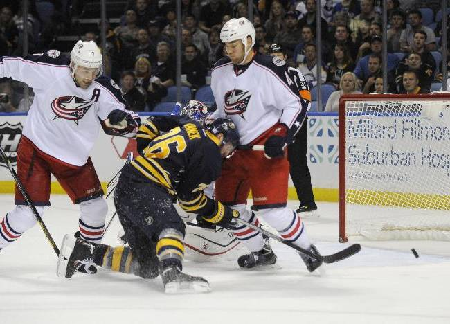 Buffalo Sabres' Thomas Vanek (26), of Austria, is checked as he shoots by Columbus Blue Jackets' Jack Johnson (7) and Dalton Prout (47) during the first period of an NHL hockey game in Buffalo, N.Y., Thursday, Oct. 10, 2013
