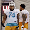 In this Nov. 4, 2013, file photo, Miami Dolphins guard John Jerry (74) talks with center Mike Pouncey during NFL football practice in Davie, Fla. Dolphins offensive lineman Jonathan Martin was subjected to
