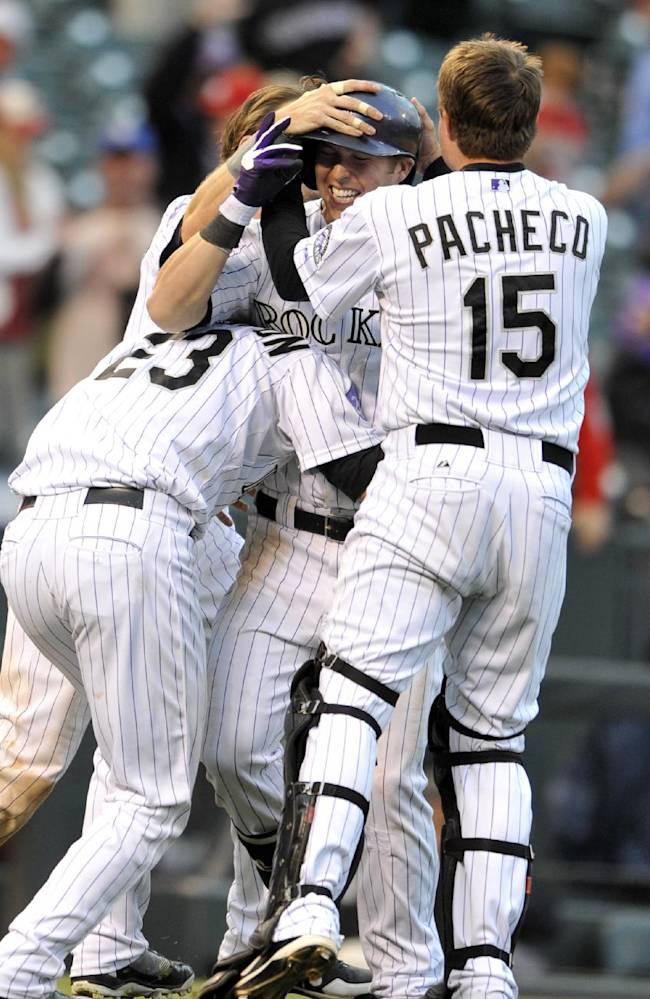 Colorado Rockies' Corey Dickerson (6) is mobbed by teammates Charlie Culberson (23) and Jordan Pacheco (15) after hitting the running RBI off St. Louis Cardinals relief pitcher Fernando Salas during the 15th inning of a baseball game on Thursday, Sept. 19, 2013, in Denver. The Rockies beat the Cardinals 7-6 in 15 innings