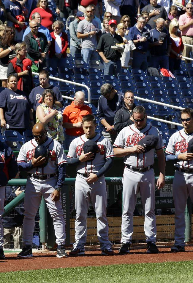 The Atlanta Braves observe a moment of silence before a baseball game against the Washington Nationals at Nationals Park Tuesday, Sept. 17, 2013, in Washington, to honor those killed and injured in Monday's attack at the nearby Washington Navy Yard