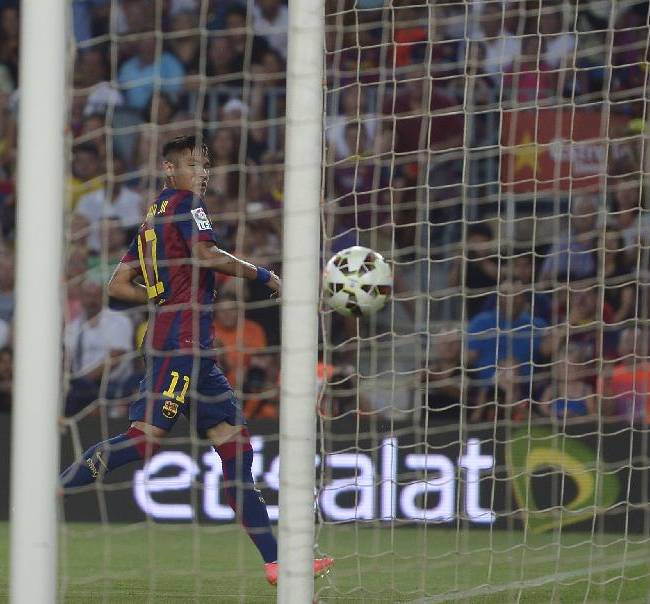 Barcelona's Neymar, from Brazil, looks to the ball after scoring against Leon at the Camp Nou in Barcelona, Spain, Monday, Aug. 18, 2014