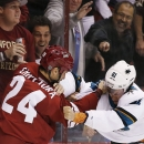 Arizona Coyotes' Kyle Chipchura (24) and San Jose Sharks' Justin Braun (61) figh during the first period of a preseason NHL hockey game Friday, Oct. 3, 2014, in Glendale, Ariz The Associated Press