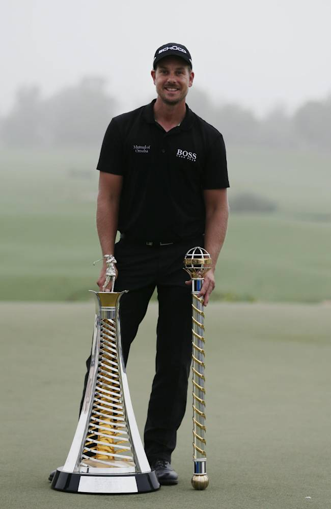 Henrik Stenson from Sweden poses for picture with the European tour race to Dubai and DP World Golf Championship trophies after the final round of DP World Golf Championship, in Dubai, United Arab Emirates, Sunday, Nov. 17, 2013