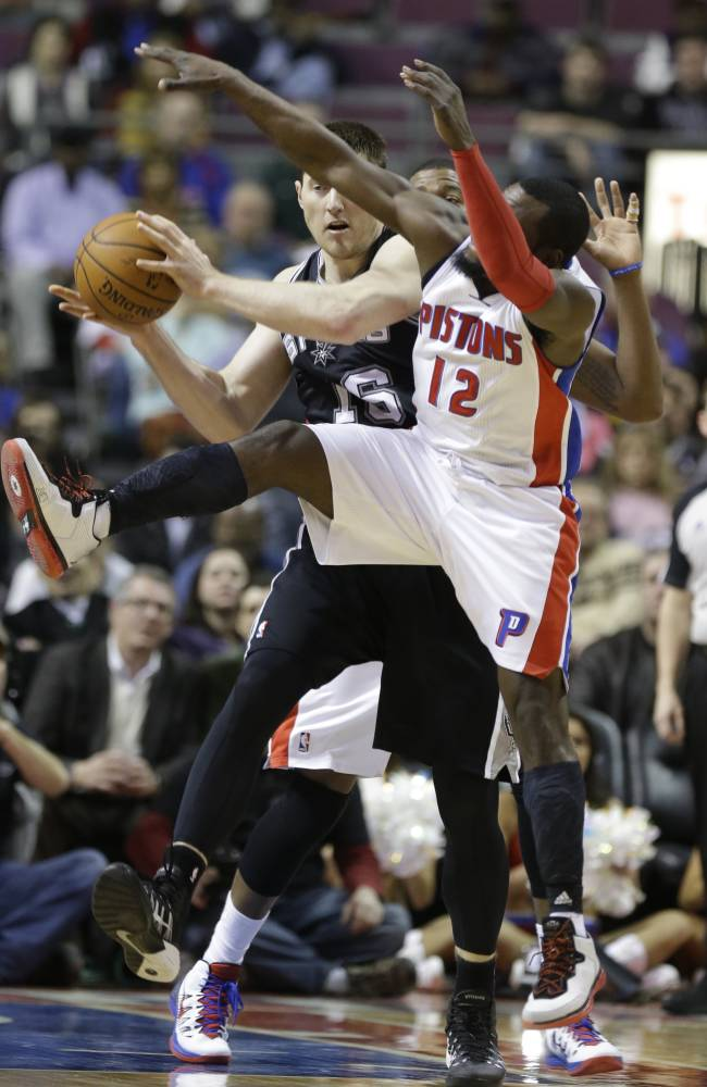 San Antonio Spurs forward Aron Baynes (16) controls the ball as Detroit Pistons guard Will Bynum (12) reaches in during the second half of an NBA basketball game in Auburn Hills, Mich., Monday, Feb. 10, 2014