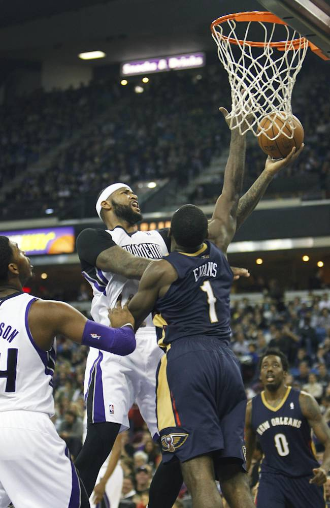 Sacramento Kings center DeMarcus Cousins, left, drives to the basket against New Orleans Pelicans defender Tyreke Evans during the second half of an NBA basketball game in Sacramento, Calif.,  on Monday, Dec. 23, 2013. The Pelicans won 113-100