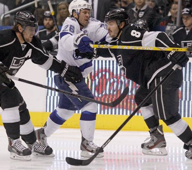 Tampa Bay Lightning right wing Martin St. Louis, center, is stopped by Los Angeles Kings defenseman Drew Doughty, right, with center Anze Kopitar (11), of Yugoslavia defending in the first period of an NHL hockey game Tuesday, Nov. 19, 2013, in Los Angeles. St. Louis is playing in his 1,000th career game