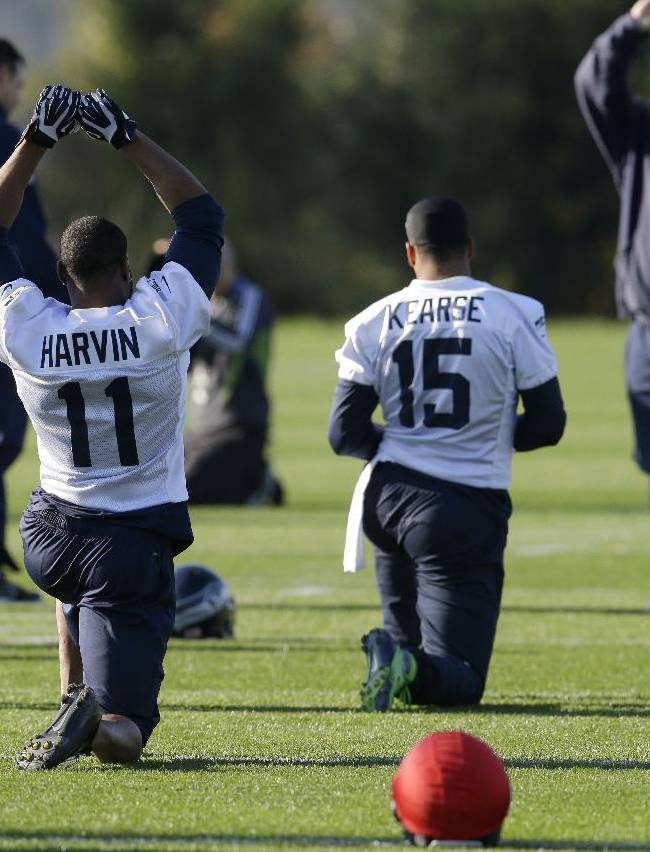 Seattle Seahawks wide receiver Percy Harvin (11) stretches with teammates as wide receivers coach Kippy Brown looks on at left, at the start of NFL football practice, Tuesday, Oct. 22, 2013, in Renton, Wash. It was Harvin's first full team practice since he injured his hip during the off-season
