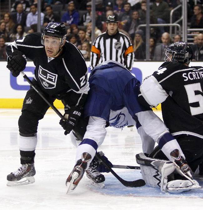 Los Angeles Kings defenseman Alec Martinez, left, keeps his eyes on the puck as Tampa Bay Lightning right wing Brett Connolly, center, falls through the crease, sandwiched in a battle with Kings goalie Ben Scrivens, right, in the third period of an NHL hockey game Tuesday, Nov. 19, 2013, in Los Angeles. The Kings won 5-2