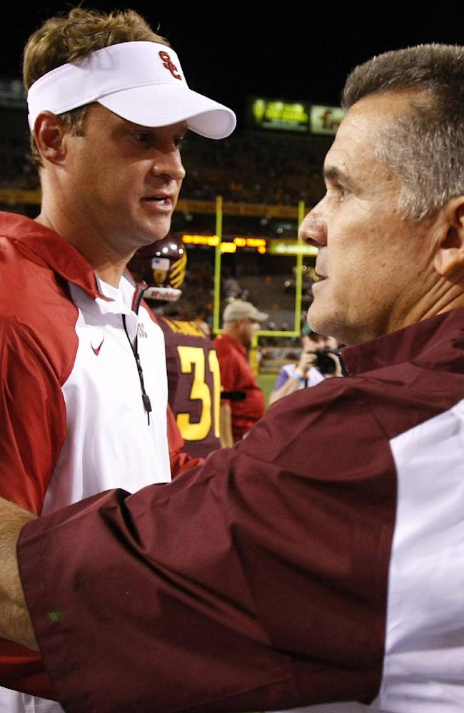 Southern California head coach Lane Kiffin shakes hands with Arizona State head coach Todd Graham after an NCAA college football game in a Saturday, Sept. 28 2013 file photo, in Tempe, Ariz. USC has fired football coach Lane Kiffin, the Trojans announced early Sunday, Sept. 29, 2013. Kiffin went 28-15 at USC in parts of four seasons, but his club has dropped seven of its last 11 games overall and is winless in a pair of Pac-12 games so far this year