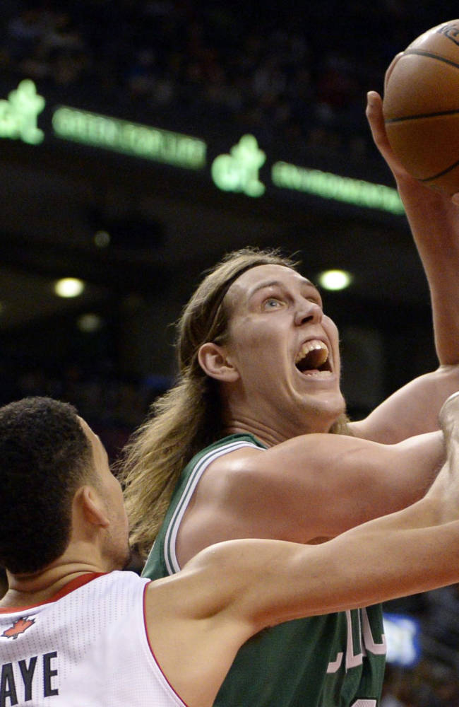 Toronto Raptors' Austin Daye, left, picks up a foul on Boston Celtics' Kelly Olynyk as Olynk drives to the basket during first half of an NBA preseason basketball game in Toronto on Wednesday, Oct. 16, 2013