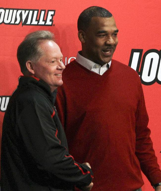 Louisville coach Bobby Petrino introduces his new offensive coordinator Garrick McGee at a new conference Monday, Jan. 13, 2014, in Louisville, Ky. McGee was the former UAB head coach