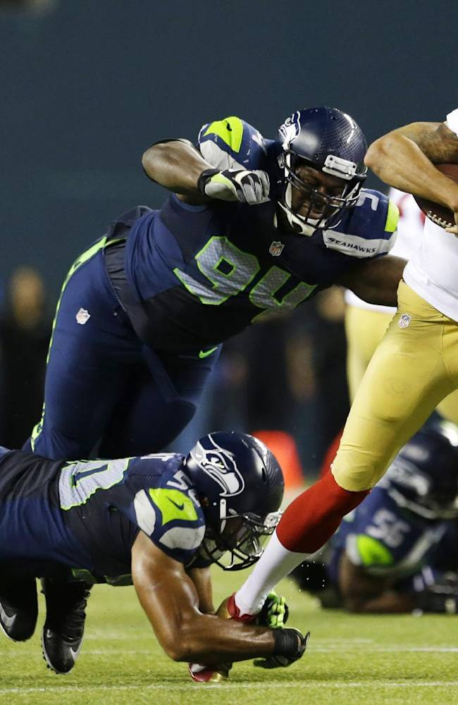 Seattle Seahawks K.J. Wright, left, and D'Anthony Smith give chase to San Francisco 49ers quarterback Colin Kaepernick in the second half of an NFL football game, Sunday, Sept. 15, 2013, in Seattle. The Seahawks won 29-3