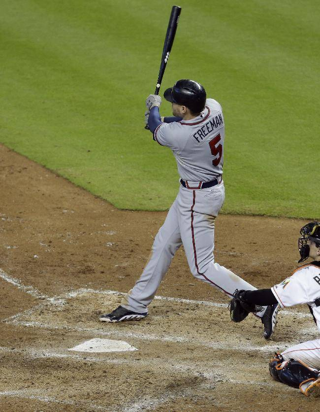 Atlanta Braves' Freddie Freeman (5) hits a a two-run home run in the fourth inning during a baseball game against the Miami Marlins, Thursday, Sept. 12, 2013, in Miami. At right is Marlins catcher Rob Brantly