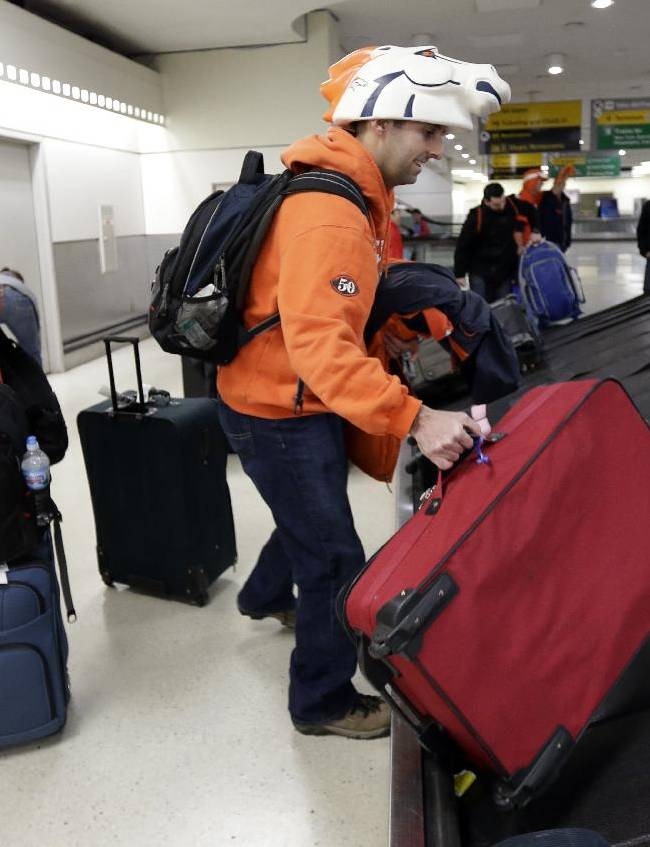 Danny Compton, of Colorado Springs, Colo., grabs his bag as his wife Andrea Compton looks on as they arrive to Newark International Airport for the Super Bowl Thursday, Jan. 30, 2014. The Seattle Seahawks will play the Denver Broncos Sunday in the NFL Super Bowl XLVIII football game in East Rutherford, N.J. (AP Photo)