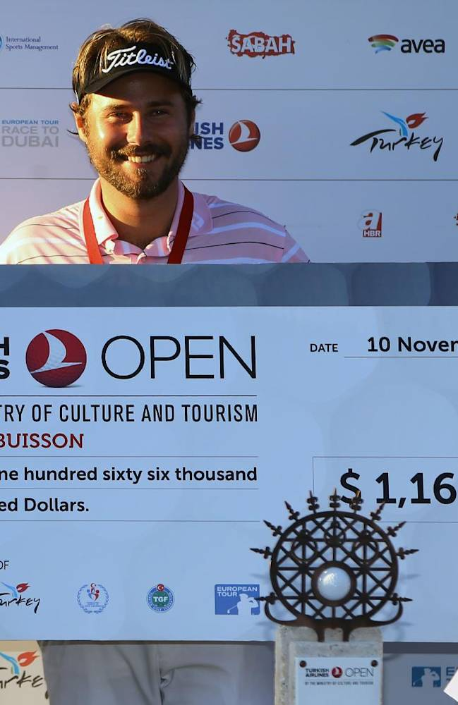 Victor Dubuisson of France smiles as he shows his prize after his victory in the Turkish Open golf tournament at the Montgomerie Maxx Royal Course in Antalya, Turkey, Sunday, Nov. 10, 2013