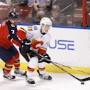 Florida Panthers defenseman Dmitry Kulikov (7) and Calgary Flames left wing Ken Agostino (51) fight for the puck during the first period of an NHL hockey game in Sunrise, Fla., Friday, April 4, 2014 The Associated Press