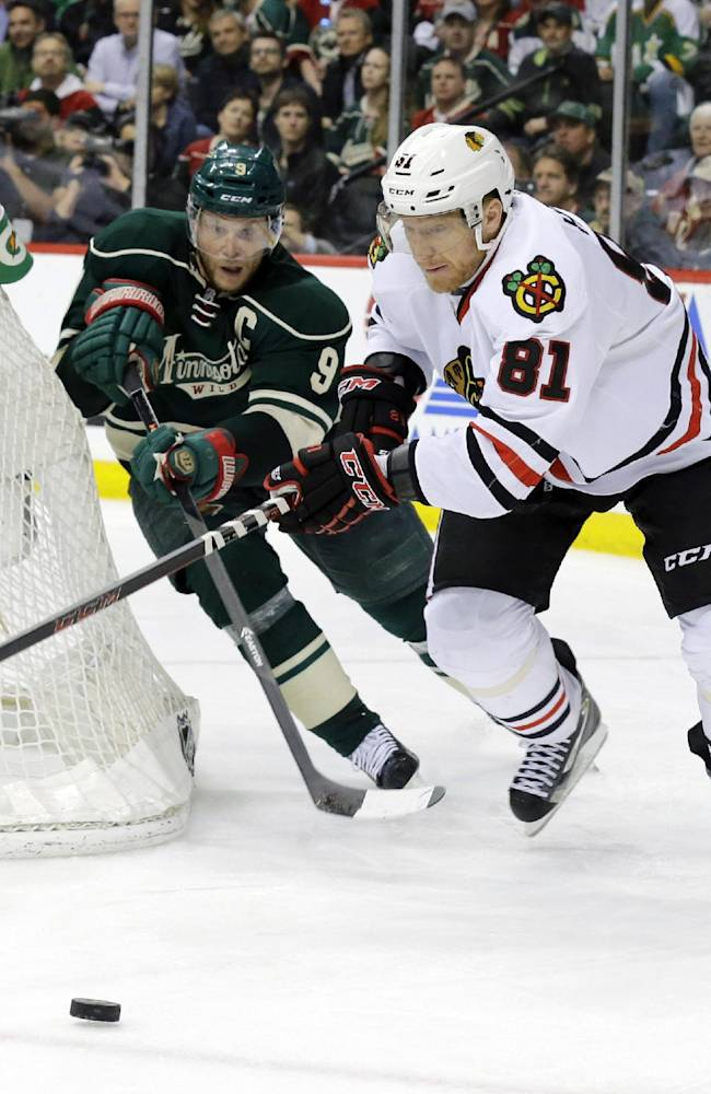 Chicago Blackhawks right wing Marian Hossa (81), of Czech Republic, and Minnesota Wild center Mikko Koivu (9), of Finland, chase the puck during the second period of Game 6 of an NHL hockey second-round playoff series in St. Paul, Minn., Tuesday, May 13, 2014. The Blackhawks won 2-1 in overtime