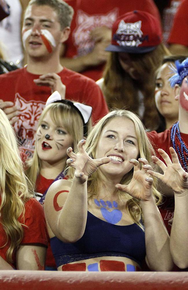 Arizona Wildcat fans show their spirit against Utah with a cat claw roar in the first half of an NCAA college football game, Saturday, Oct. 19, 2013 in Tucson, Ariz