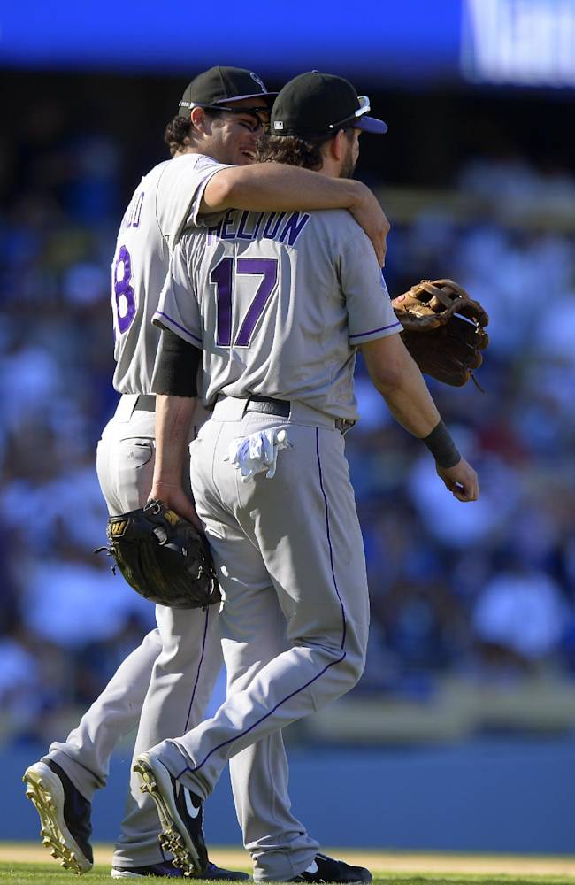 Colorado Rockies' Nolan Arenado, left, hugs Todd Helton after the Rockies defeated the Los Angeles Dodgers 2-1 in a baseball game, Sunday, Sept. 29, 2013, in Los Angeles. Helton was playing in the final game of his career