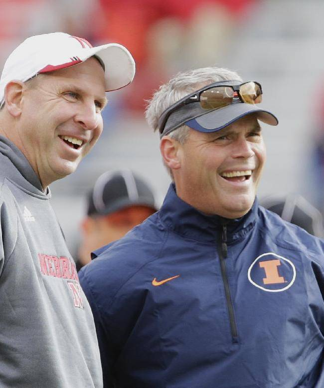 Nebraska head coach Bo Pelini, left, and Illinois head coach Tim Beckman share a light moment during warm ups before an NCAA college football game in Lincoln, Neb., Saturday, Oct. 5, 2013