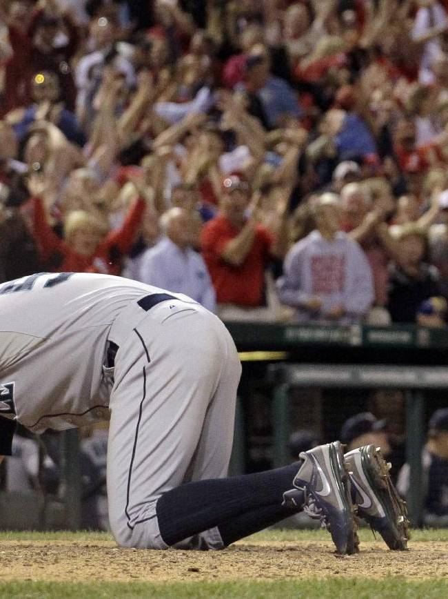 Seattle Mariners relief pitcher Oliver Perez stays on the ground for a moment after St. Louis Cardinals' Pete Kozma scored the game-winning run on a passed ball during the 10th inning of a baseball game Friday, Sept. 13, 2013, in St. Louis. The Cardinals won 2-1