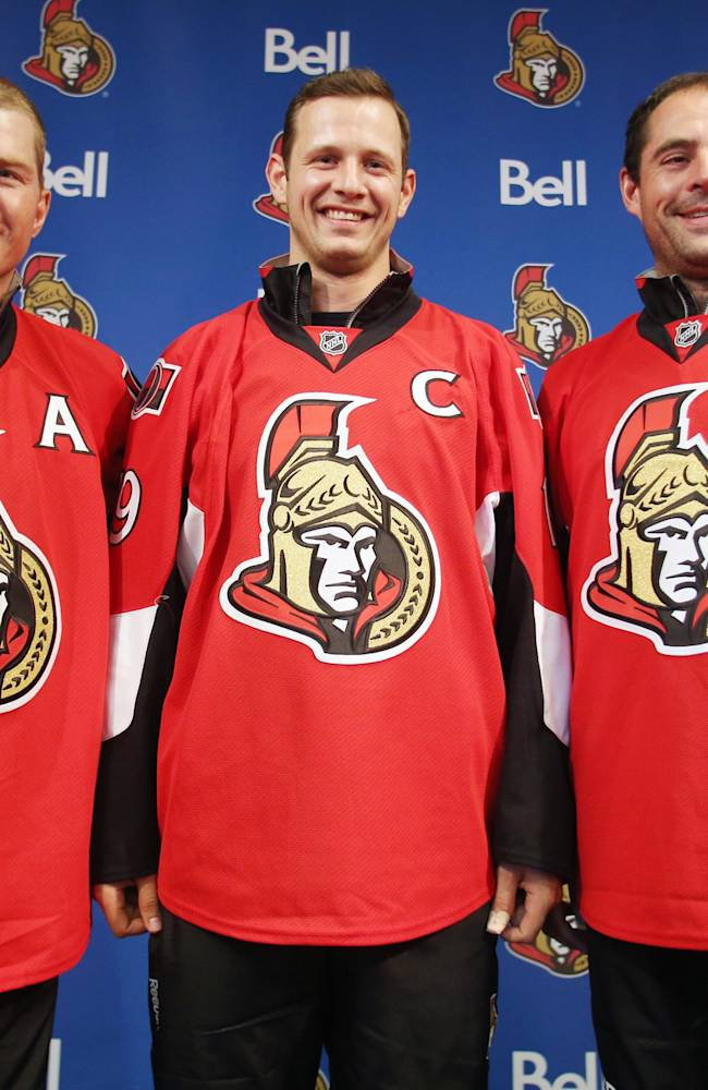 Ottawa Senators captain Jason Spezza, center, poses with teammates and assistant captains Chris Neil, left, and Chris Phillips after Spezza was announced as the NHL hockey team's captain in Ottawa, Ontario, Saturday Sept. 14, 2013