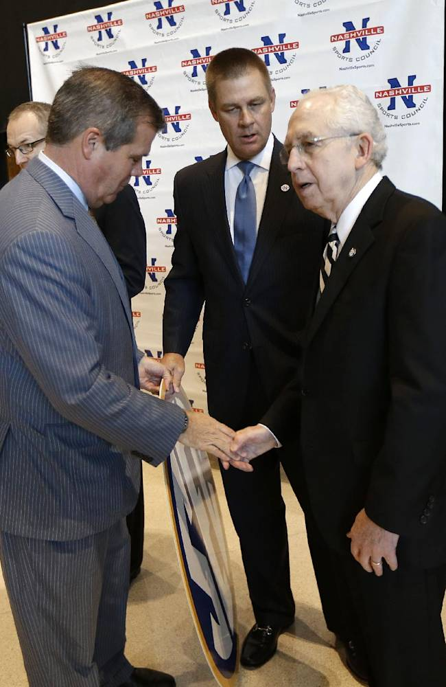 Southeastern Conference Commissioner Mike Slive, right, shakes hands with Nashville, Tenn., Mayor Karl Dean, left, at Bridgestone Arena on Tuesday, Oct. 15, 2013, in Nashville, Tenn. Slive earlier announced a deal with the Nashville Sports Council to hold nine men's NCAA SEC college basketball tournaments at the facility in 2015-2017, 2019-2021 and 2023-2025. The deal also includes dates for three women's tournaments in 2018, 2022 and 2026. At center is Scott Ramsey, president of the Nashville Sports Council