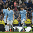 Manchester City players including Samir Nasri, second left, react after Wigan Athletic's second goal during their English FA Cup quarterfinal soccer match at the Etihad Stadium, Manchester, England, Sunday, March 9, 2014. Wigan won the game 2-1