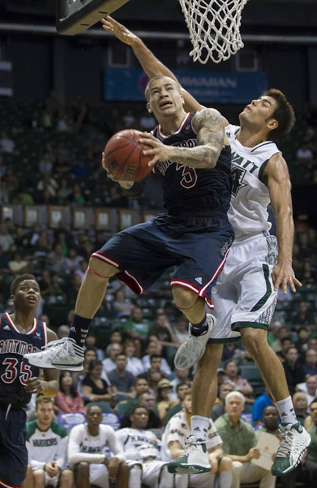 St. Mary's guard Kerry Carter (3) ducks under Hawaii forward Christian Standhardinger, right, and shoots a reverse layup in the first half of an NCAA college basketball game at the Diamond Head Classic Monday, Dec. 23, 2013, in Honolulu