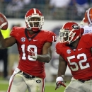 Georgia cornerback Sanders Commings (19) holds up the ball next to teammate Amarlo Herrera (52) after he recovered a fumble in the endzone by Florida tight end Jordan Reed late in the second half of an NCAA college football game, Saturday, Oct. 27, 2012, in Jacksonville, Fla. (AP Photo/John Raoux)