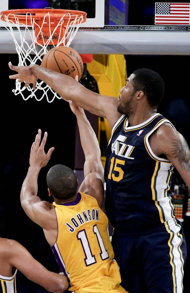 Utah Jazz forward Derrick Favors, right, fouls Los Angeles Lakers guard Wesley Johnson during the first half of a preseason NBA basketball game in Los Angeles, Tuesday, Oct. 22, 2013