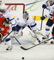 Tampa Bay Lightning goalie Ben Bishop, center, watcjes as Calgary Flames' Mike Cammalleri, left, and Lee Stempniak chase the puck in front of him during the second period of an NHL hockey game Friday, Jan. 3, 2014, in Calgary, Alberta. (AP Photo/The Canadian Press, Jeff McIntosh)