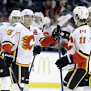 Calgary Flames left wing Mike Cammalleri (13) celebrates with teammates, including Mikael Backlund (11), of Sweden, and T.J. Brodie (7), after scoring against the Tampa Bay Lightning during the first period of an NHL hockey game on Thursday, April 3, 2014