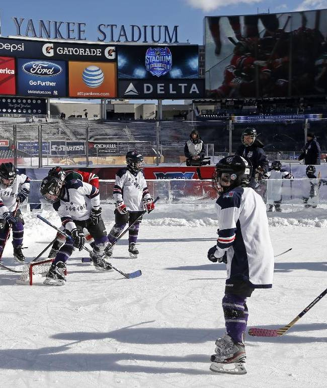 Youngsters from various NHL diversity teams use the practice ice before an NHL outdoor hockey game between the New York Rangers and the New Jersey Devils at Yankee Stadium in New York, Sunday, Jan. 26, 2014