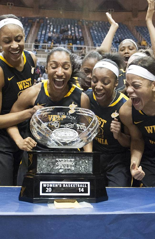 West Virginia's women's basketball team celebrates a share of the Big 12 Conference championship after defeating Kansas during an NCAA college basketball game Tuesday, March 4, 2014, in Morgantown, W.Va. West Virginia won 67-60