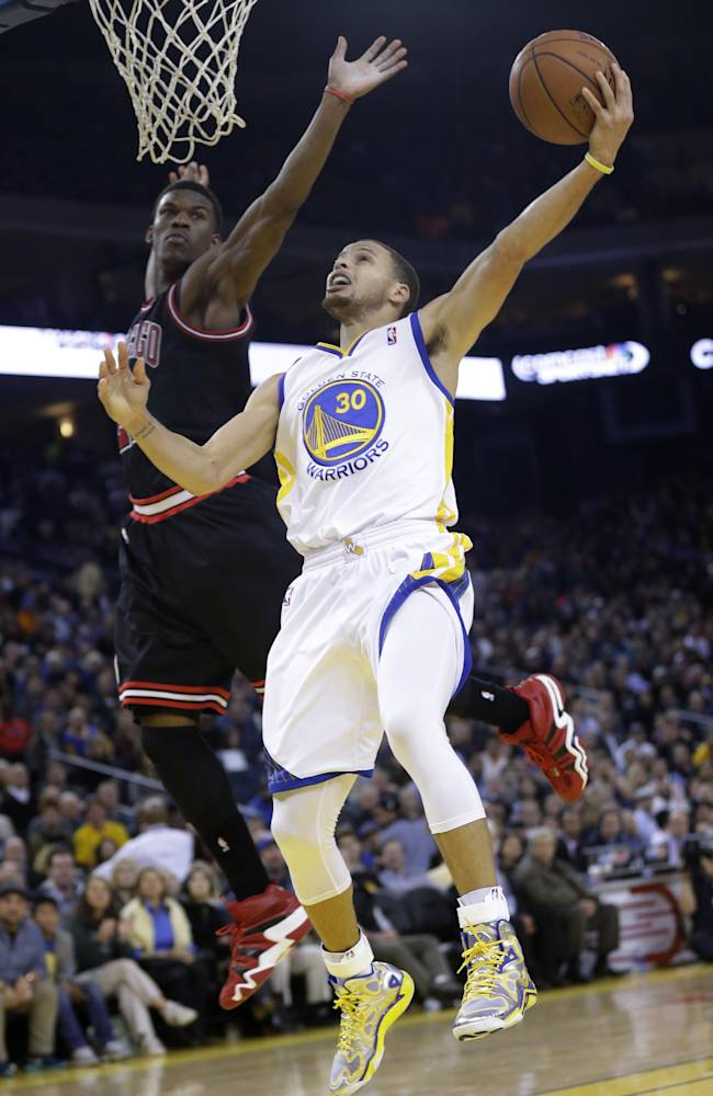 Golden State Warriors' Stephen Curry (30) scores past Chicago Bulls' Jimmy Butler during the second half of an NBA basketball game on Thursday, Feb. 6, 2014, in Oakland, Calif. Golden State won 102-87