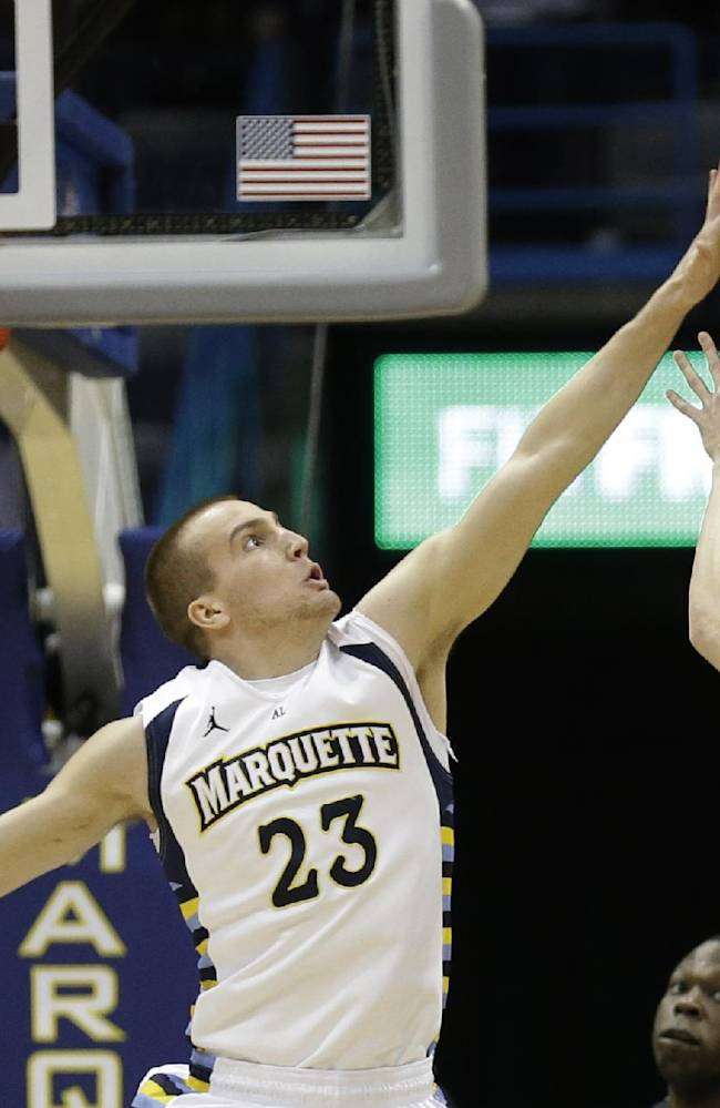 CORRECTS MARQUETTE PLAYER'S NAME - Marquette's Jake Thomas (23) blocks the shot of Butler's Kellen Dunham (24) during the first half of an NCAA college basketball game, Tuesday, Feb. 4, 2014, in Milwaukee