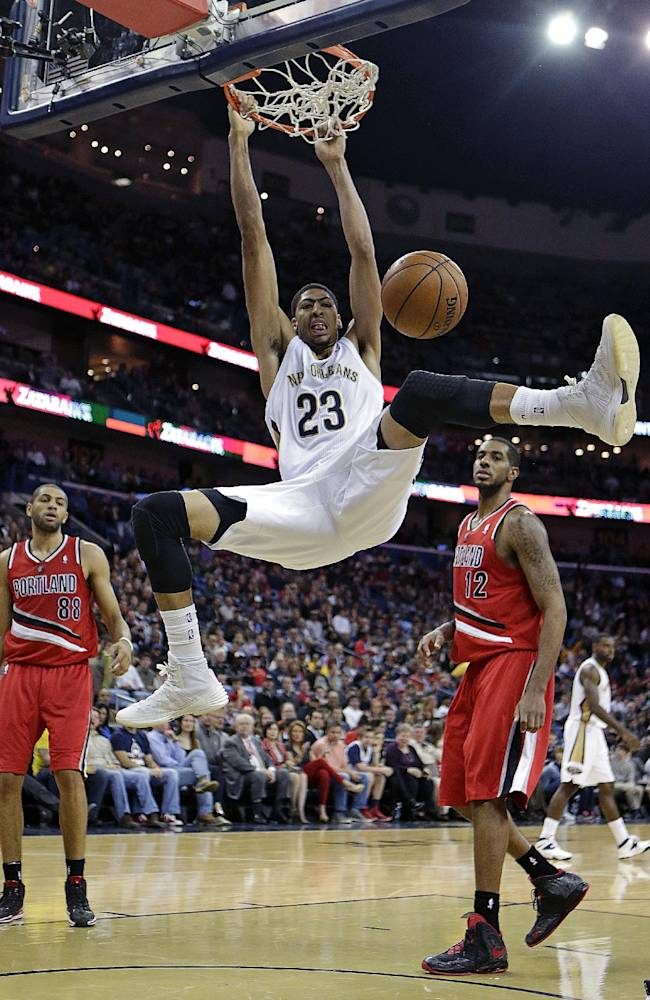 New Orleans Pelicans forward Anthony Davis (23) slam dunks in front of Portland Trail Blazers forwards LaMarcus Aldridge (12) and Nicolas Batum (88) in the second half of an NBA basketball game in New Orleans, Monday, Dec. 30, 2013. The Pelicans won 110-108