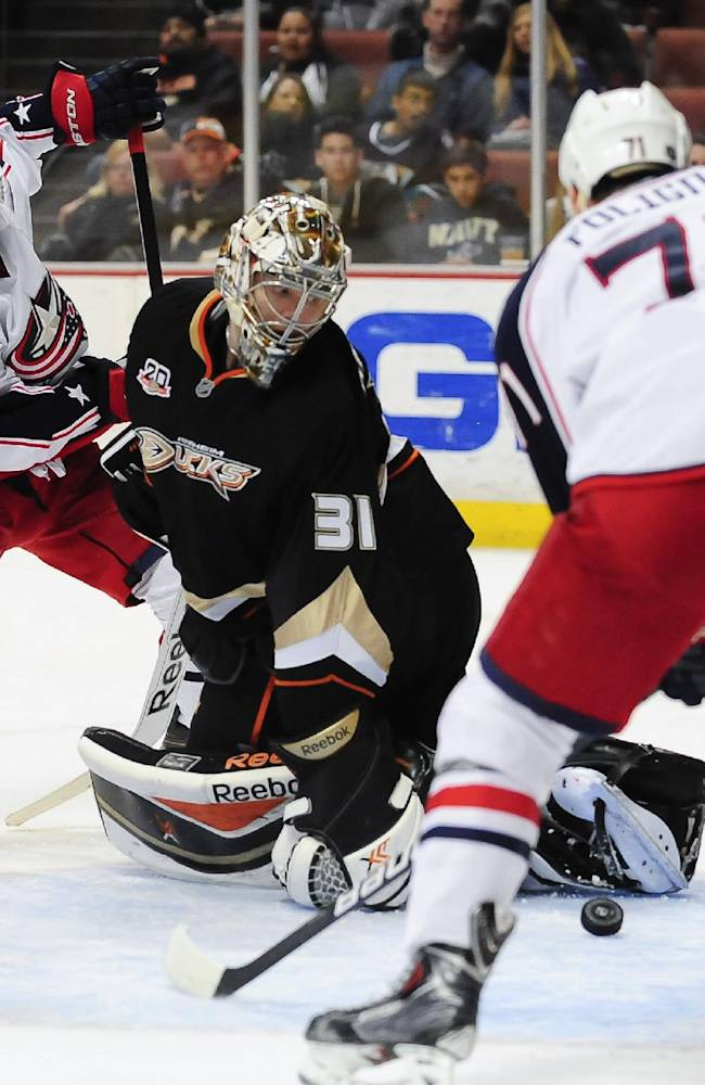 Columbus Blue Jackets right wing Cam Atkinson (13) assists teammate left wing Nick Foligno (71) as he scores on Anaheim Ducks goalie Frederik Andersen (31) during the third period of an NHL hockey game, Monday, Feb. 3, 2014, in Anaheim, Calif. The Blue Jackets won 4-2