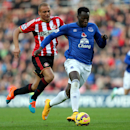 Everton's Romelu Lukaku, controls the ball with Sunderland's Wes Brown, left, during their English Premier League soccer match at the Stadium of Light, Sunderland, England, Sunday, Nov. 9, 2014