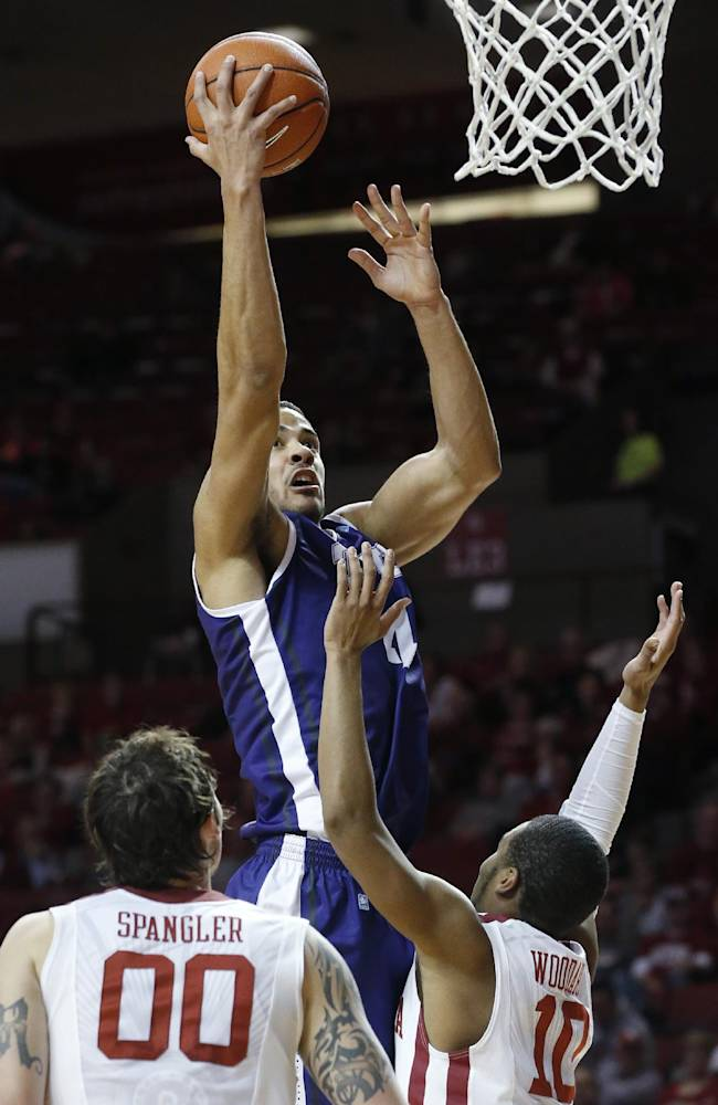 TCU forward Amric Fields (4) shoots in front of Oklahoma forward Ryan Spangler (00) and guard Jordan Woodard (10) during the first half of an NCAA college basketball game in Norman, Okla., Wednesday, Jan. 22, 2014. Oklahoma won 77-69
