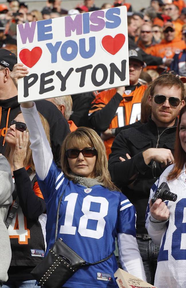 In this Nov. 4, 2012, file photo, a fan wearing and Indianapolis Colts jersey holds up a sign for Denver Broncos quarterback Peyton Manning during the first half of an NFL football game in Cincinnati. Manning returns to Indianapolis on Sunday, to face his old team for the first time since signing with the Broncos