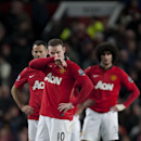 Manchester United's Wayne Rooney, center, wipes his face after a goal by Everton's Bryan Oviedo during their English Premier League soccer match at Old Trafford Stadium, Manchester, England, Wednesday Dec. 4, 2013