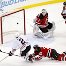 The puck enters the net of New Jersey Devils goalkeeper Keith Kinkaid (1) on a shot by Chicago Blackhawks defenseman Duncan Keith (2) as Devils' Mike Sislo (32) tries to defend during the third period of an NHL hockey game, Tuesday, Dec. 9, 2014, in Newar