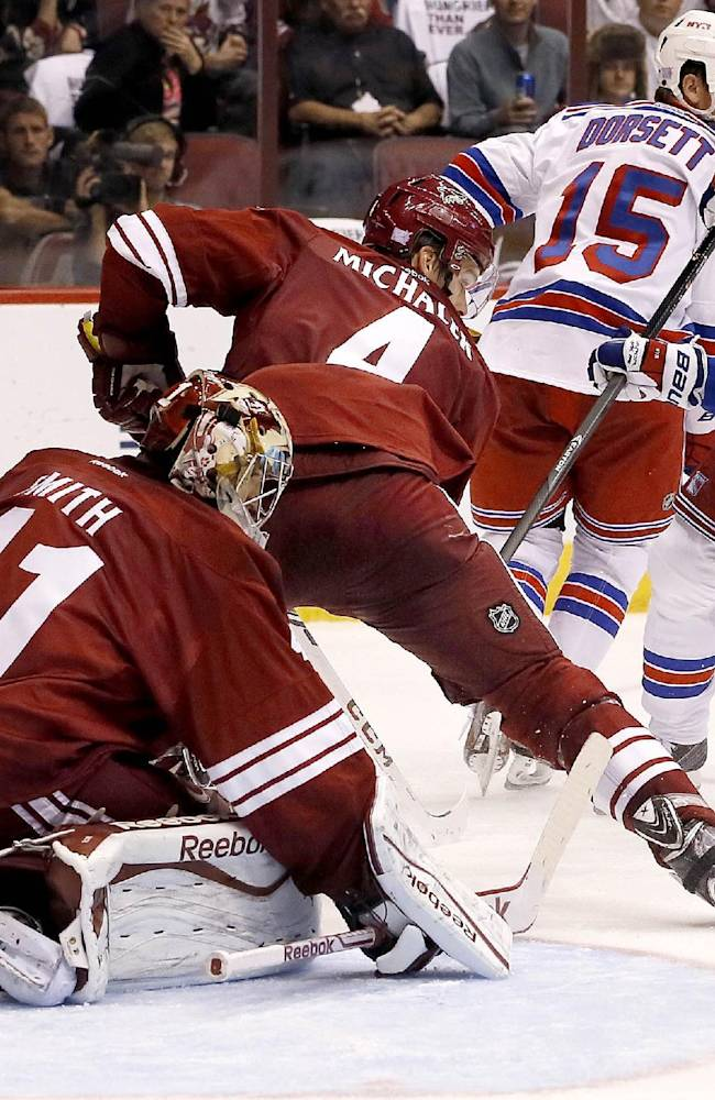 New York Rangers' Dominic Moore (28) sends the puck wide past Phoenix Coyotes' Mike Smith (41) as Coyotes' Zbynek Michalek (4), of the Czech Republic, defends and Rangers' Derek Dorsett (15) looks on in the second period during an NHL hockey game on Thursday, Oct. 3, 2013, in Glendale, Ariz.  The Coyotes defeated the Rangers 4-1