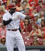 Cincinnati Reds' Brandon Phillips points to the dugout as he stands on first base after getting a hit off Pittsburgh Pirates starting pitcher A.J. Burnett to drive in a run in the first inning of a baseball game on Saturday, July 20, 2013, in Cincinnati. (AP Photo/Al Behrman)